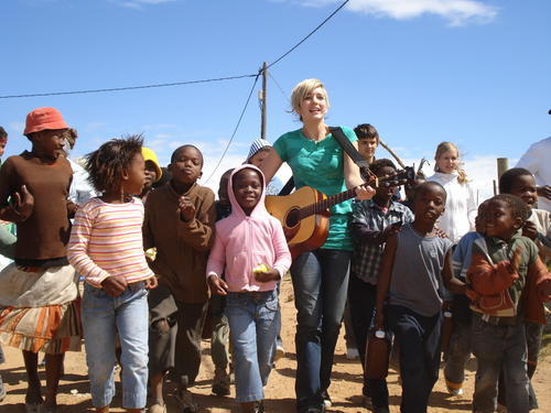 Blond woman playing guitar and singing with children in South Africa