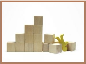 Building block pyramid broken, human figure toppled