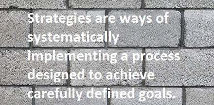 definition printed on photo of block wall: Strategies are ways of systematically implementing a process designed to achieve carefully defined goals.
