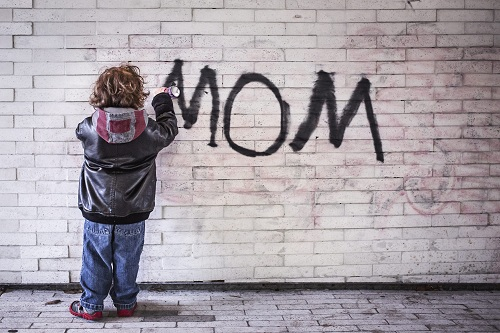 small boy spray-painting MOM on wall