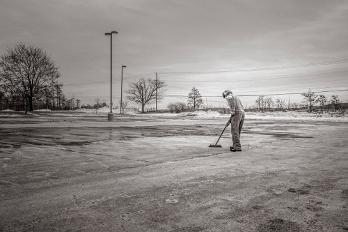 man sweeping big parking lot with broom