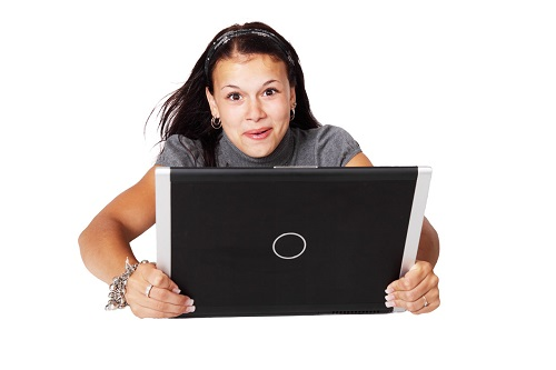 woman looks up from computer in pleasant surprise